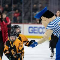 Louie the Laker high fives young hockey players